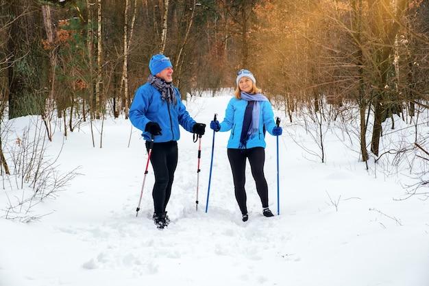 Пожилая пара гуляет с палками для скандинавской ходьбы в снежном зимнем парке