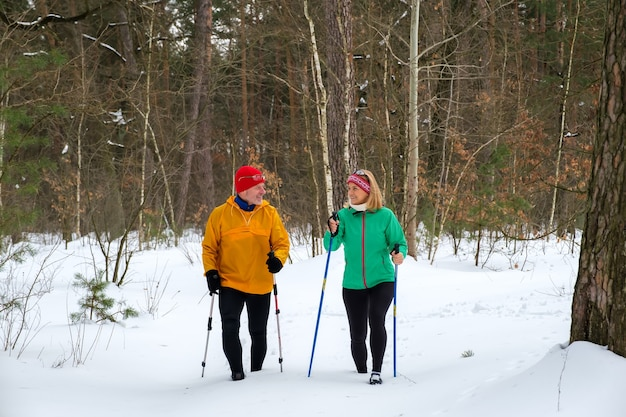 Senior couple walking with nordic walking poles in snowy winter forest