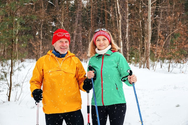Senior couple walking with nordic walking poles in snowy winter park
