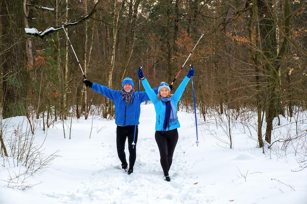 눈 덮인 겨울 공원에서 뻗은 팔을 걷고 수석 부부