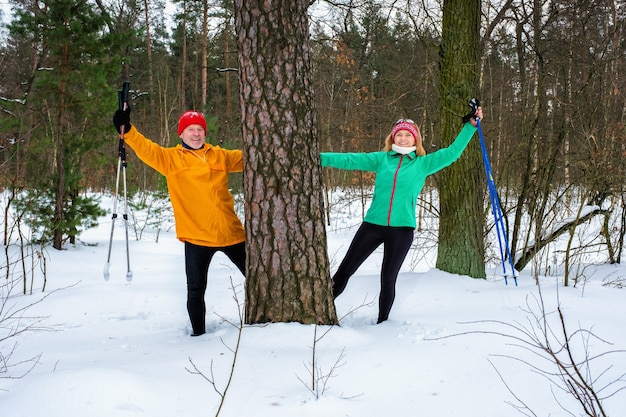 Senior couple walking with outstretched arms in snowy winter forest