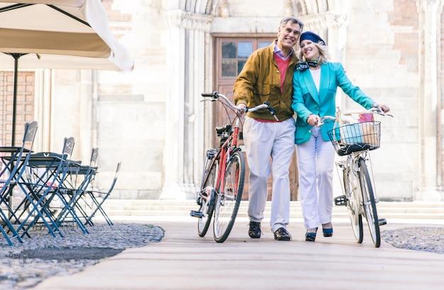 Пожилая пара гуляет с велосипедом в центре города