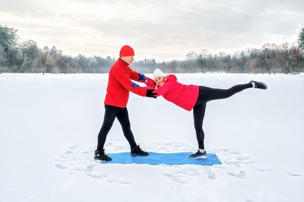 Пожилая пара разогревается перед разминкой и делает растяжку перед тренировкой