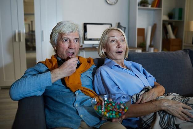 映画を見ている年配のカップル