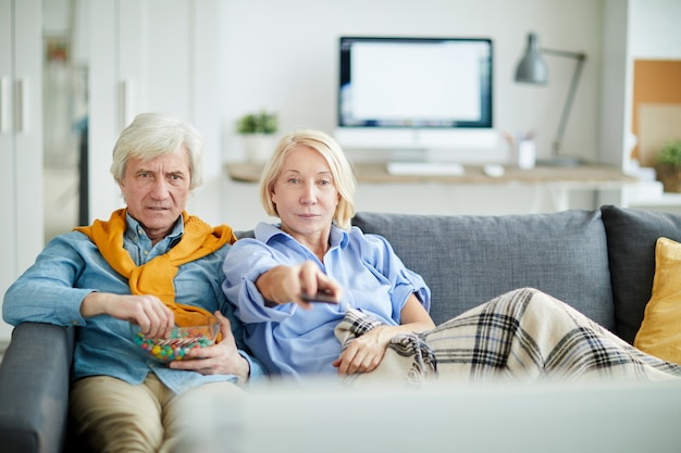 テレビを見ている年配のカップル