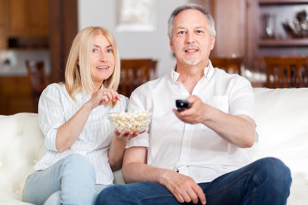 Senior couple watching tv and eating pop-corn