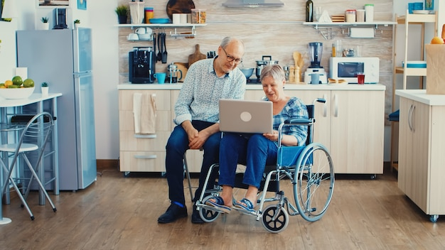 キッチンのラップトップでビデオ通話中にウェブカメラで手を振っている年配のカップル。現代の通信技術を使用して、オンライン通話で障害のある老婆とその夫を麻痺させた。
