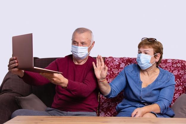 Senior couple waving while having a video call on laptop at home on sofa social distancing during covid coronavirus quarantine lockdown holidays in quarantine new normal