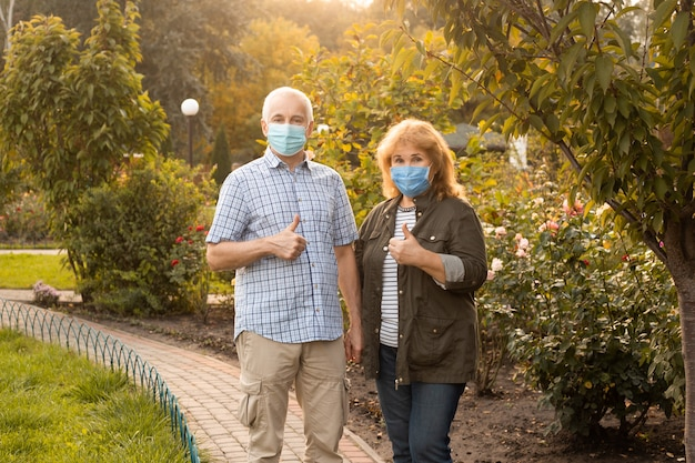 Senior couple wearing masks showing thumbs up