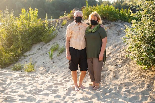 夏の自然の外でコロナウイルスから保護するために医療マスクを身に着けている年配のカップル、コロナウイルス検疫