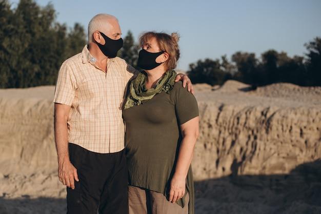 夏の日にコロナウイルスから保護するために医療用マスクを着用している年配のカップル、コロナウイルス検疫
