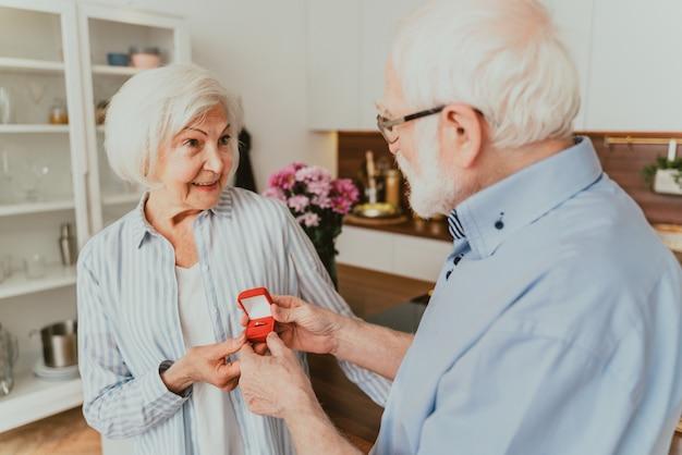Senior couple wedding proposal, - elderly man asking his woman to marry him, engagement ring gift