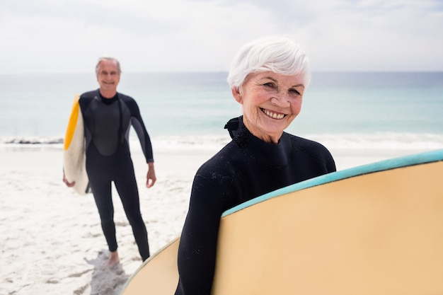 Senior couple in wetsuit holding surfboard on beach