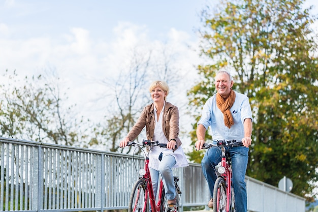 Senior couple with bicycles on bridge