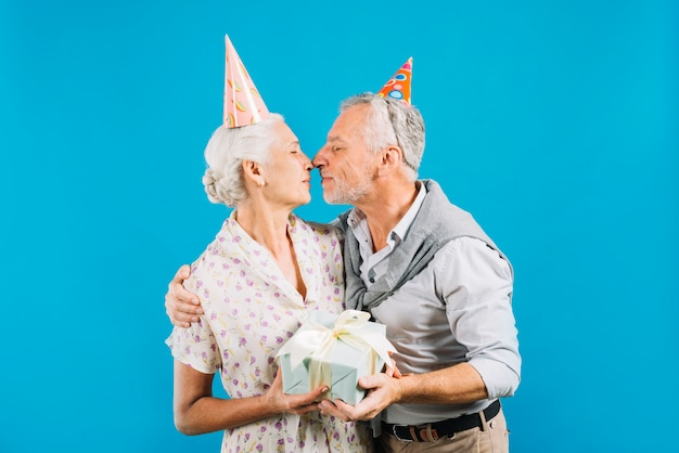 Senior couple with birthday gift loving each other on blue backdrop