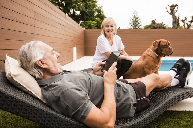 Senior couple with dog in garden