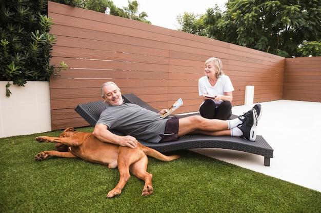 庭で犬と年配のカップル