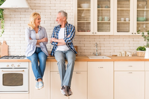 Senior couple with his arm crossed sitting on kitchen counter looking at each other