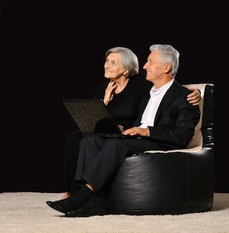 Senior couple with laptop sitting on black background