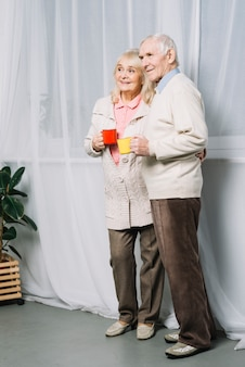 Senior couple with mugs of coffee
