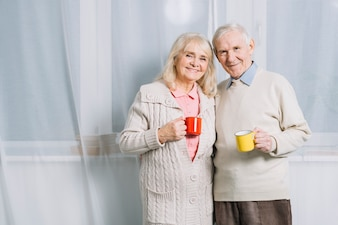 Senior couple with mugs of coffee