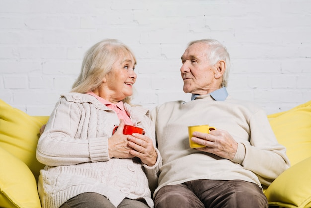 Пожилая пара с кружками кофе