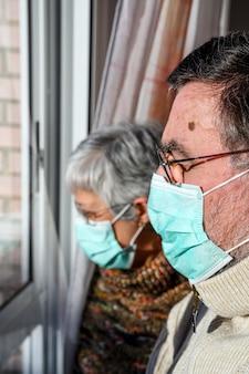 Пожилые супружеские пары, с защитными масками, дома смотрят в окно. концепция коронавируса карантина дома и социального дистанцирования.