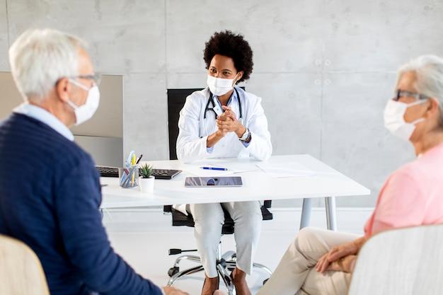 Пожилая пара с защитными масками для лица получает новости от черной женщины-врача в офисе