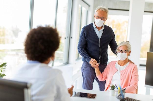 보호 얼굴 마스크와 수석 부부는 사무실에서 흑인 여성 의사의 소식을받습니다
