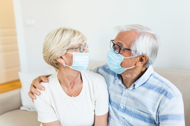 Senior couple with protective mask in quarantine at home