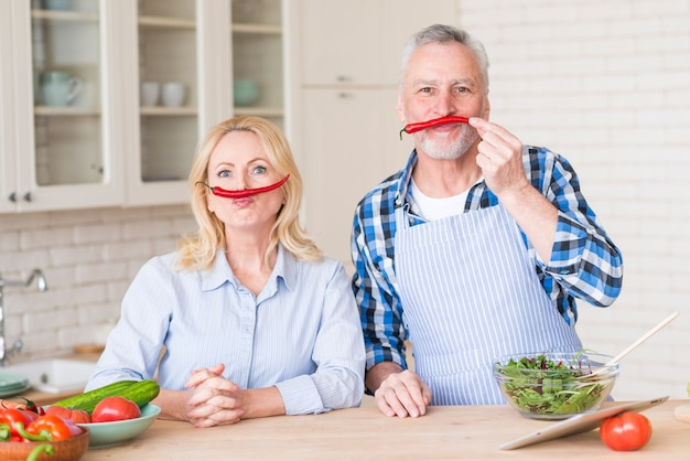 Senior couple with red chili peppers on their upper lips looking at camera