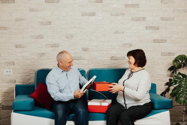 自宅のソファに座っている赤白のギフトボックスと年配のカップル。幸せな年配の女性は彼女の愛する夫から贈り物を受け取っています。