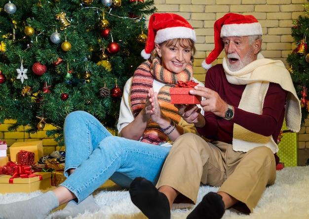 リビングルームで隣に飾られたクリスマスツリーに座っている間、興奮した顔で現在を保持し、見ているサンタクロースの帽子を持つ年配のカップル。ロマンチックな冬の休日。