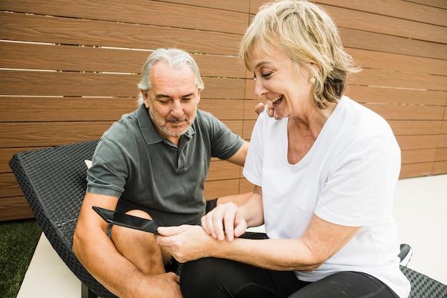 Пожилые супружеские пары с смартфон в саду