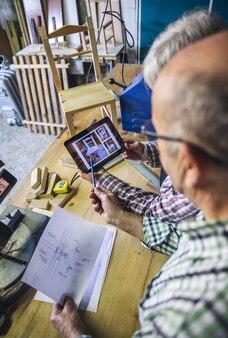 Старшая пара, работающая в столярной мастерской, глядя на планшет с дизайном стула