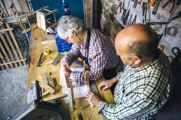 Старшая пара, работающая в столярной мастерской