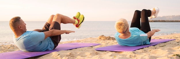 Senior couple working out together on the beach