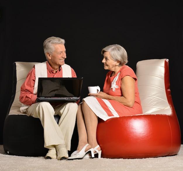 검은 배경에 앉아 노트북으로 작업하는 수석 부부