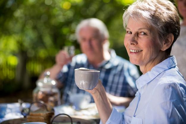 Пожилые пары завтракают в саду
