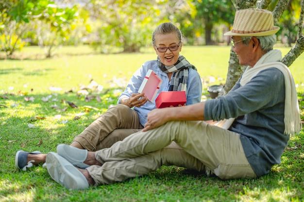 年配のカップルの退職保険高齢者のライフスタイルの概念年配のカップルは贈り物を開きます