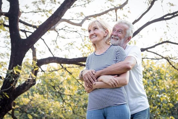 Старшие пары стоят, чтобы обнять друг друга и счастливо улыбаются в парке. счастливый улыбающийся старшей пары в парке на празднике.
