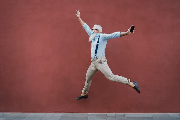 Senior crazy man jumping outdoors while wearing mask with red wall
