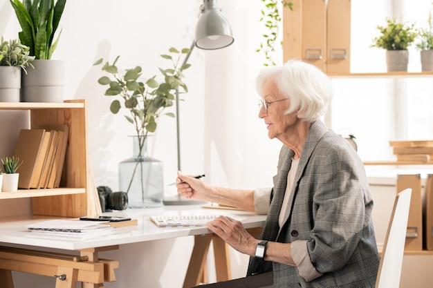 Старшая творческая женщина думает о новых идеях и записывает их в блокнот во время работы в офисе