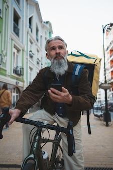 スマートフォンを使用して自転車に乗るシニア配達員