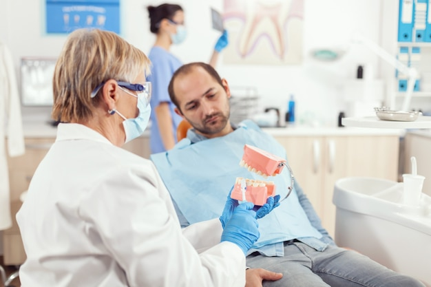 患者に歯科手術を説明する歯の顎の骨格を保持しているシニア歯科医の女性