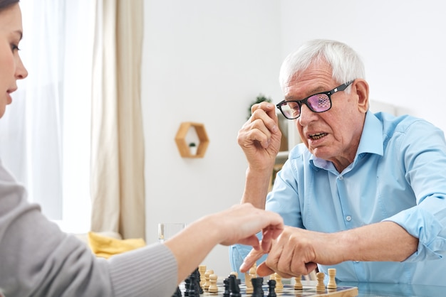 Senior disable man in eyeglasses and shirt playing chess with female social worker and explaining her rules of game