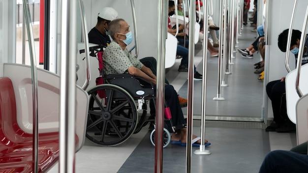 輸送のために電車で旅行中の車椅子の高齢者障害者。