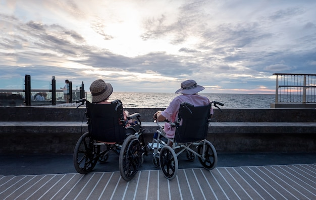 Senior disabled person in wheelchair at the beach against sunset background.