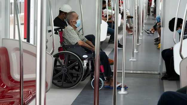 Senior disabled person in wheelchair on traveling in train for transportation.