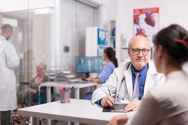 若い同僚がクリニックの廊下で車椅子の障害のある高齢の女性と話している間、病院のオフィスで女性患者に相談している先輩医師と青い制服を着た看護師がxを見て